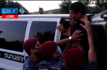 Police officers apprehend protesters near Governmental house